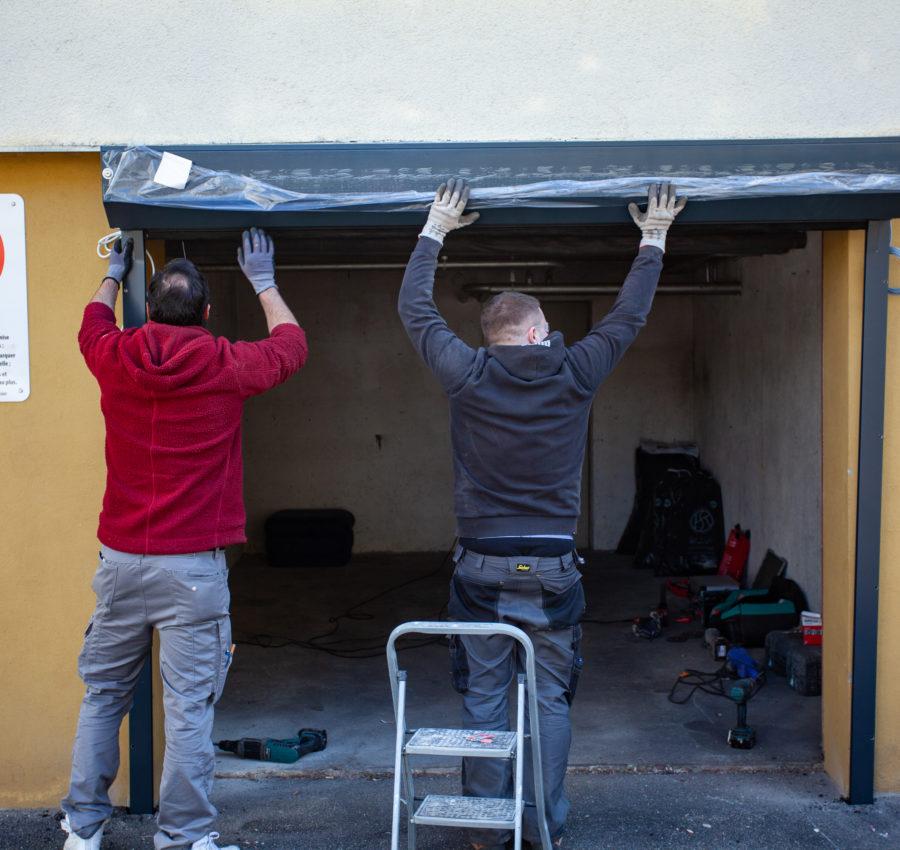 Deux ouvriers Storio pose une porte de garage