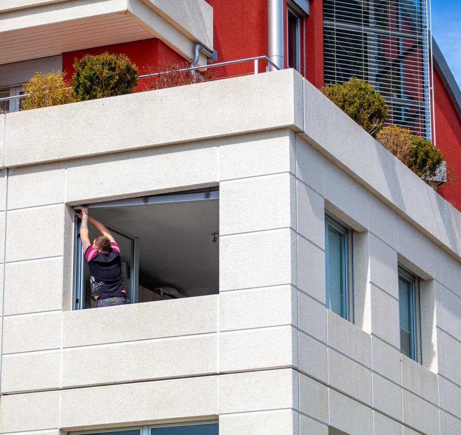 Collaborateur Storio qui pose un store à lamelle sur un immeuble